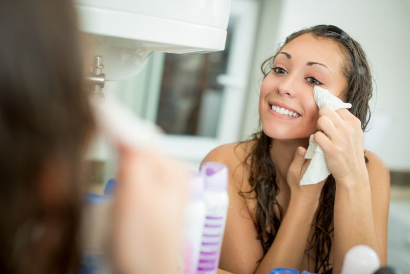 smiling woman removing her makeup