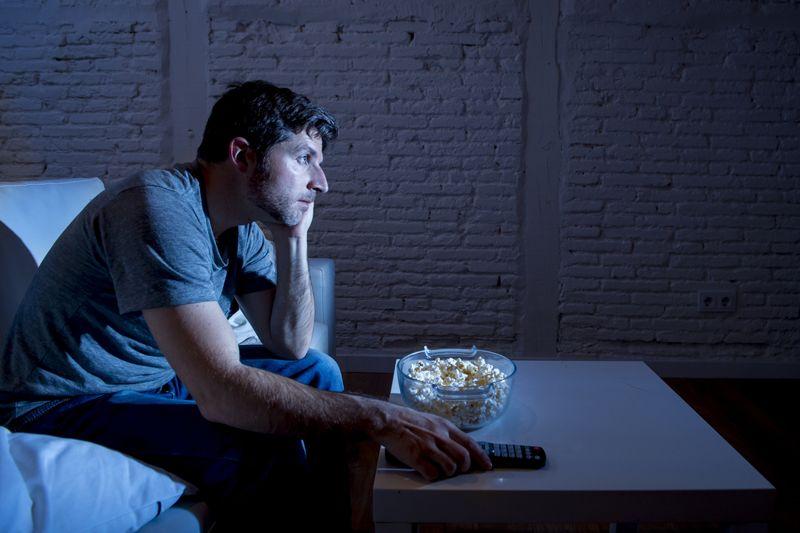 man staring at television at night