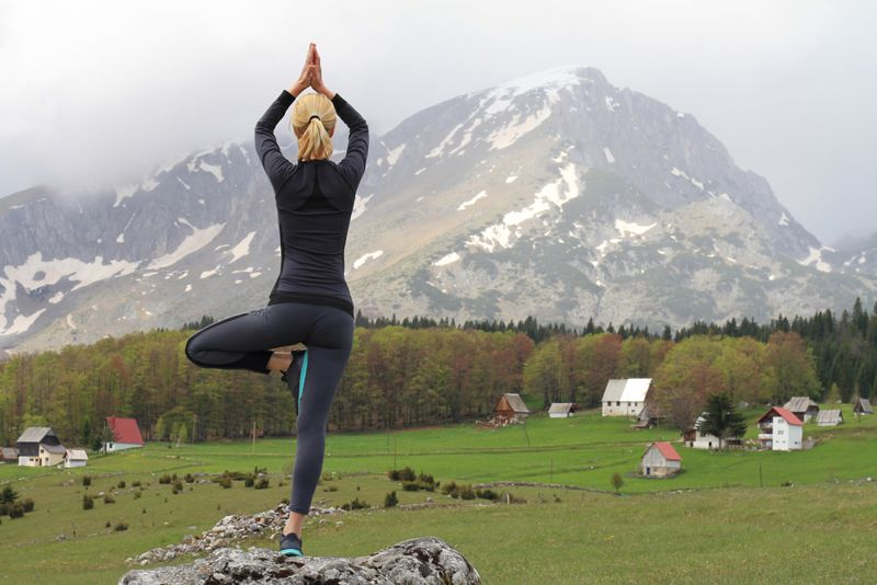 woman doing tree pose outside on a rock wall