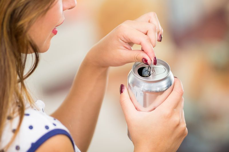 woman cracking open a can of pop or energy drink