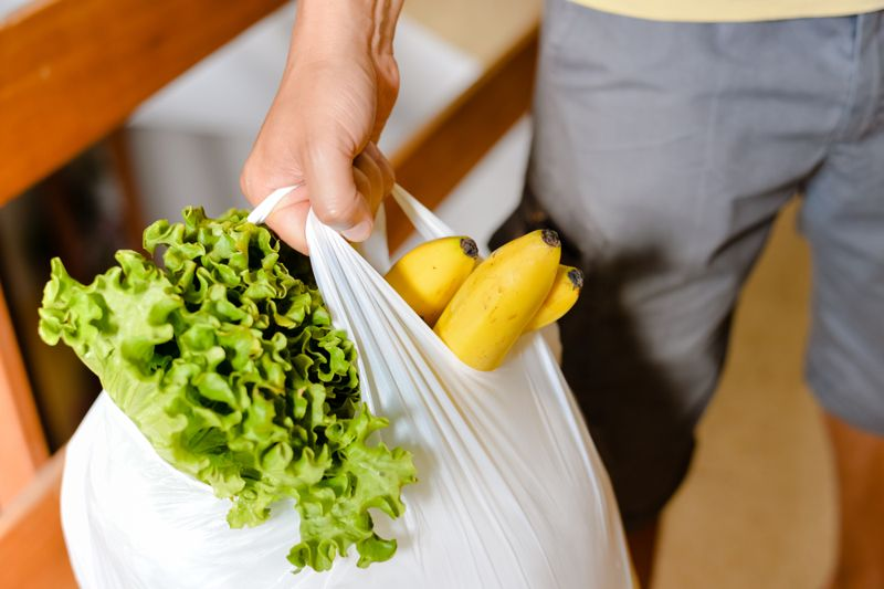 cropped image of man holding heavy bag of groceries