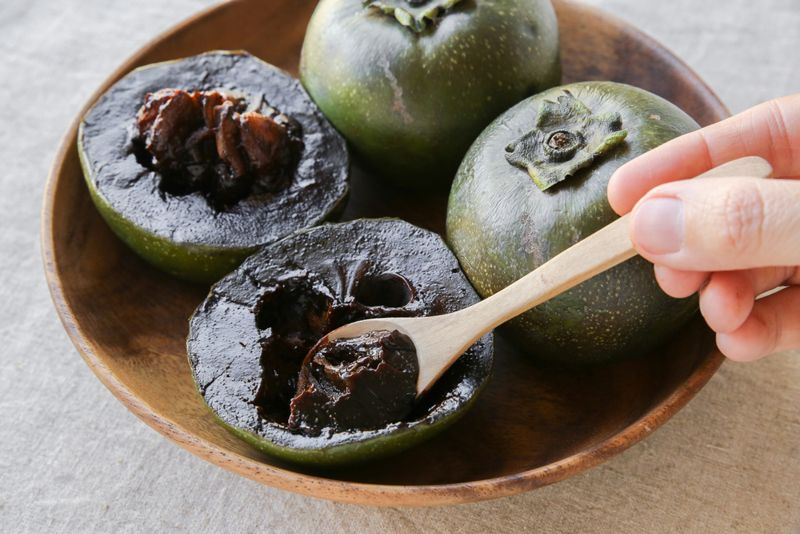 black sapote fruit cut open with spoon and wooden bowl