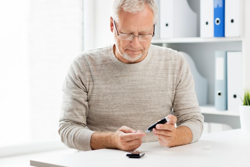 older man checking his insulin levels; diabetes concept