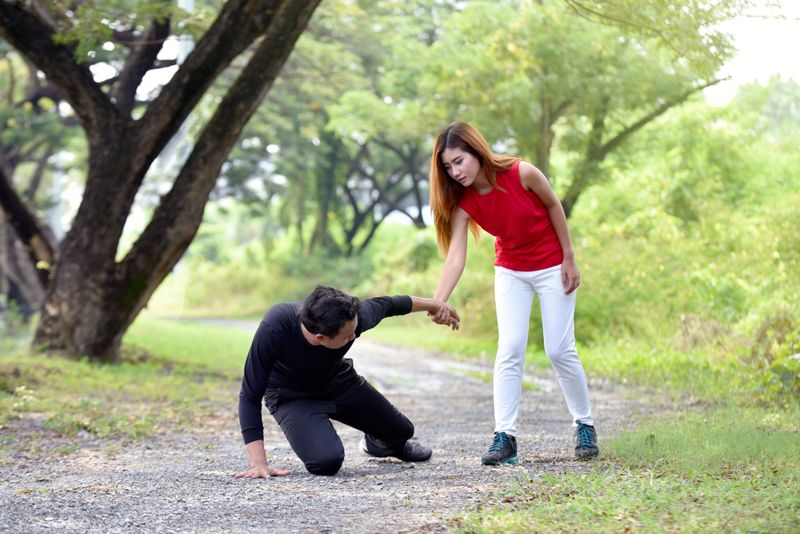 woman helping up a man who has fallen