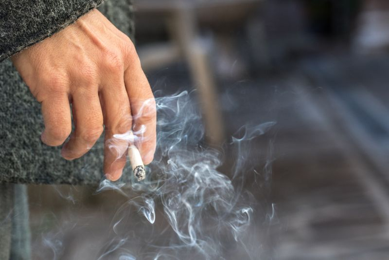cropped image of a person holding a smoking cigarette