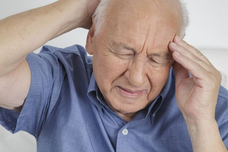 older man experiencing an intense headache