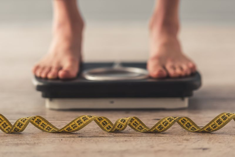 person on scale and measuring tape; weight loss concept