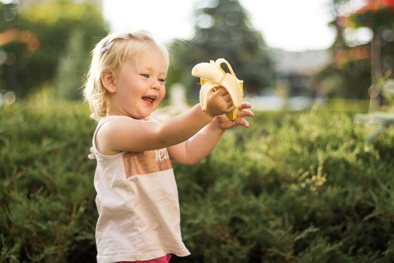 smiling toddler girl eating a banana