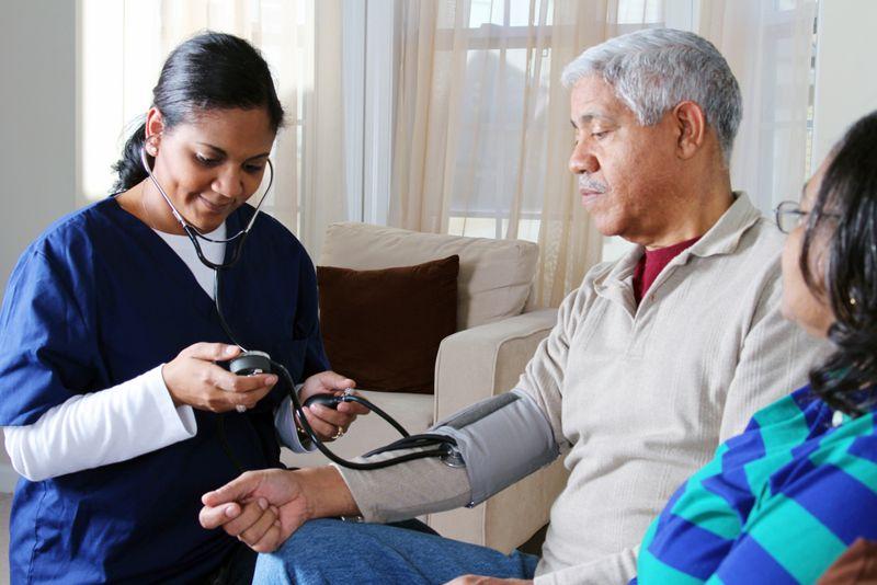 doctor checking older man's blood pressure at home