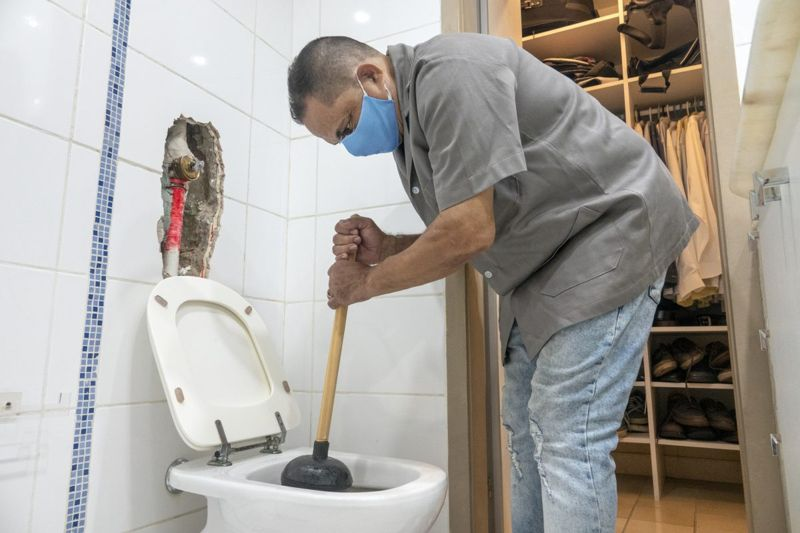 Man unclogging a toilet