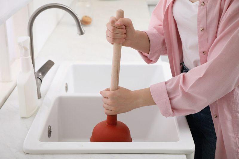 Woman unclogging a drain