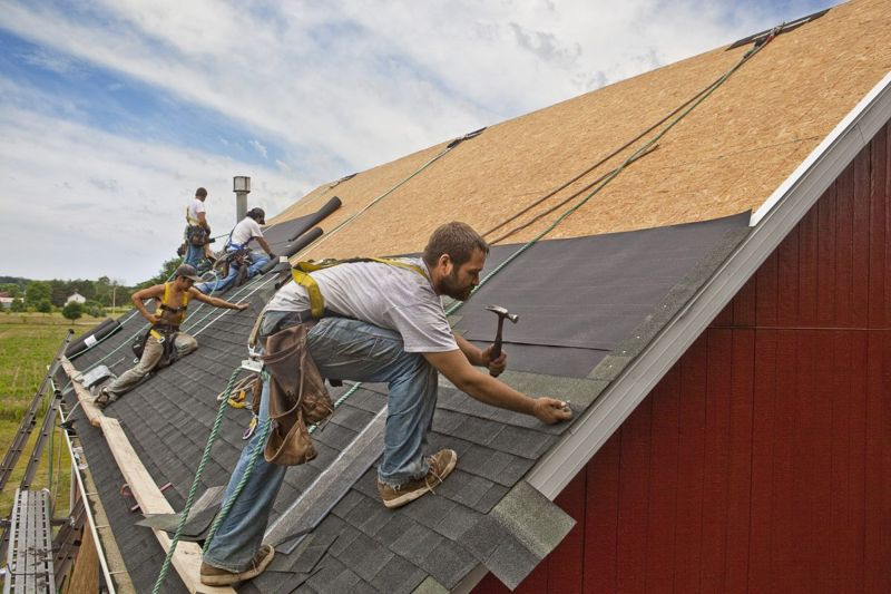 Men installing roof tiles