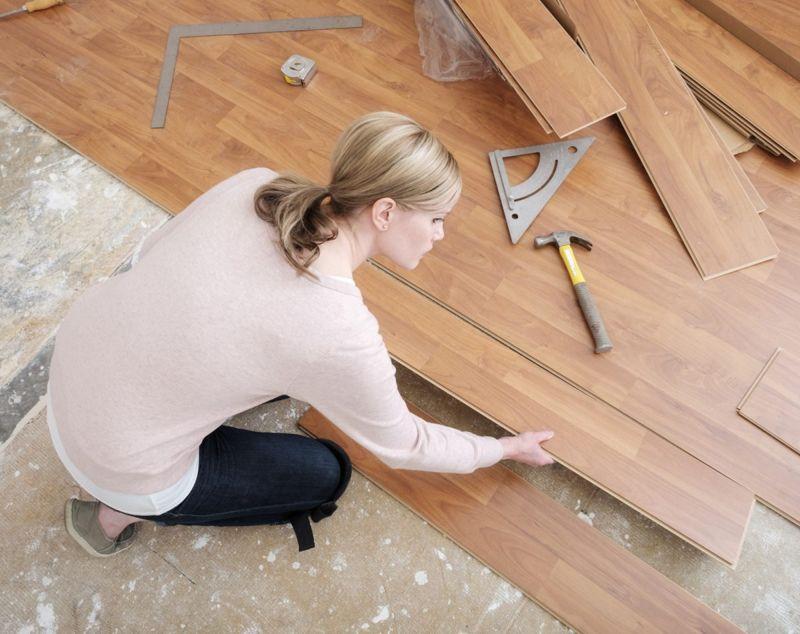 Woman installing flooring