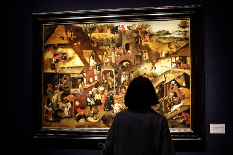 LONDON, ENGLAND - NOVEMBER 30: A visitor views 'The Netherlandish Proverbs' by Pieter Brueghel, the Younger (Brussels 1564/5-1637/8 Antwerp (estimate £3.5-5.5M) during a media preview at Christie's on November 30, 2018 in London, England. Christie's auction house in London will hold 13 sales as part of Classic Week, held from the 4th-14th December, including 200 lots from the collection of Rugby School.