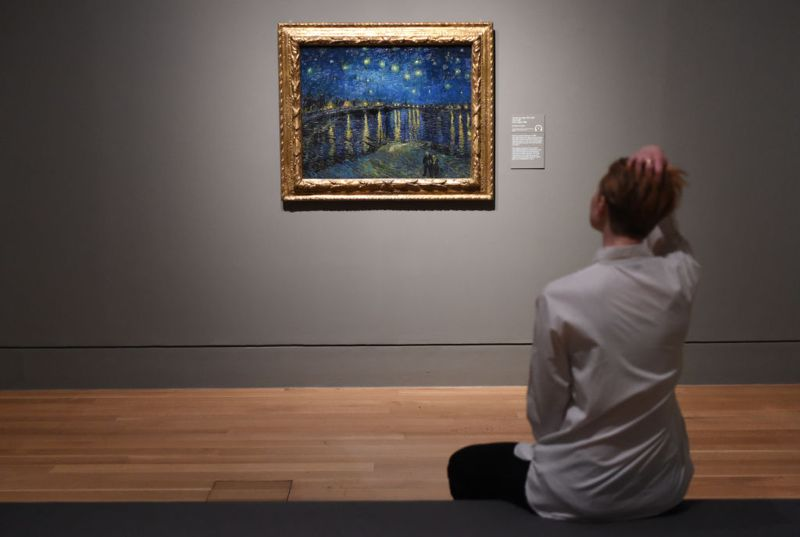 LONDON, ENGLAND - MARCH 25: People look at the painting Starry Night over the Rhone by famous Dutch artist Vincent van Gogh at the EY Exhibition: Van Gogh and Britain press day which opens at Tate Britain on March 25, 2019 in London, United Kingdom.
