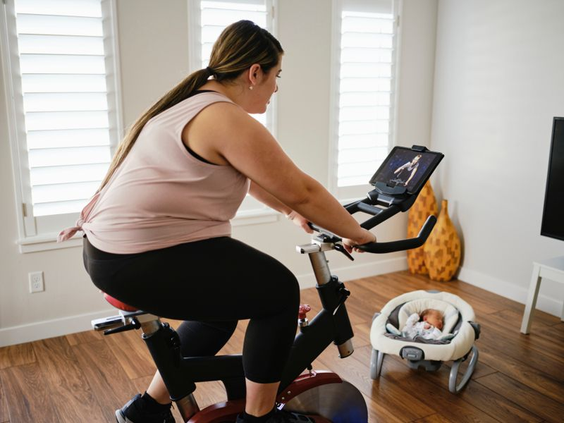 new mother on stationary bike with infant sleeping