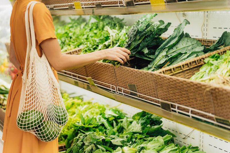 Girl is holding mesh shopping bag with avocado without plastic bags at vegetable grocery shop.