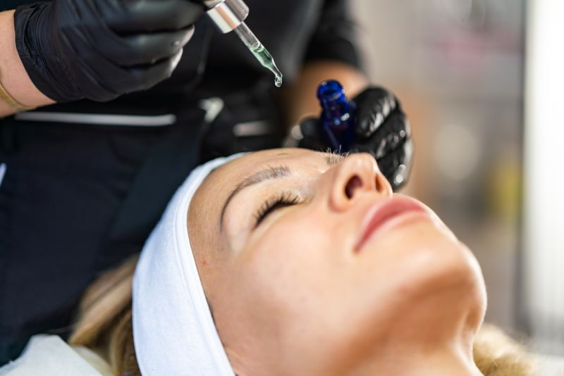 Cosmetic oil applying on face of woman