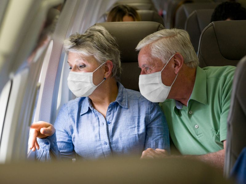 Latin American senior couple traveling by plane wearing facemasks and looking through the window - travel during the COVID-19 pandemic