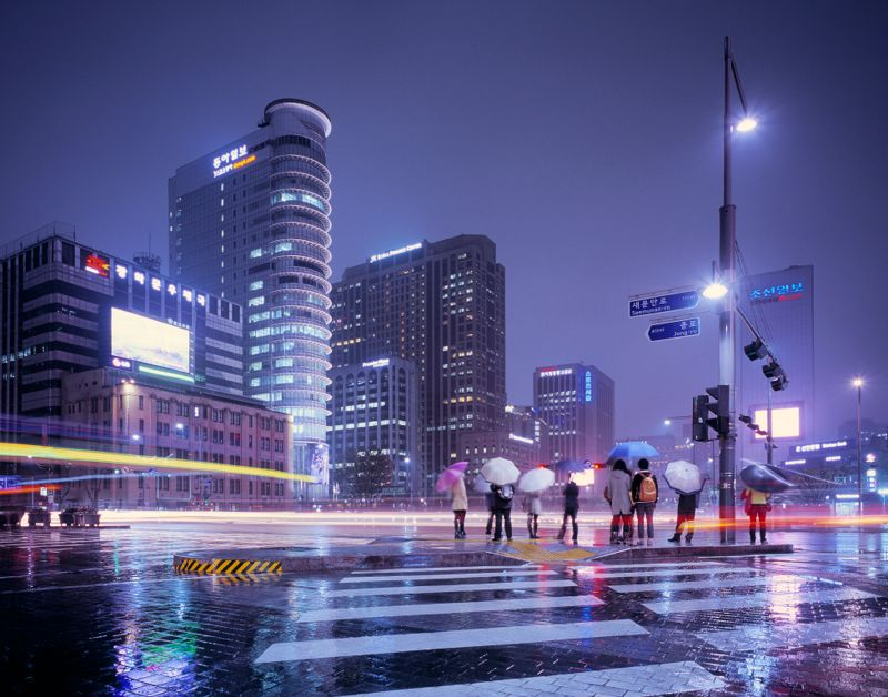 Rainy evening in Seoul with passing traffic and people waiting to cross the street, South Korea.