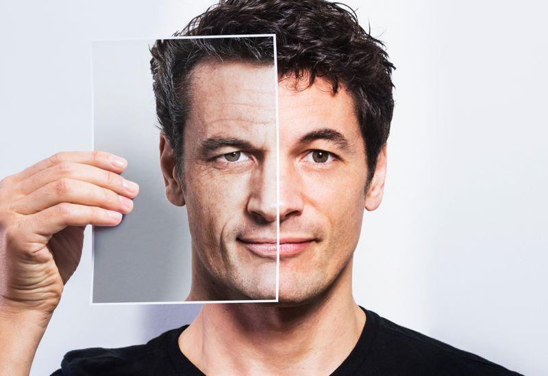 Man holding portrait of older version of himself