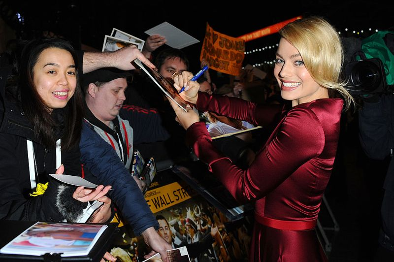 Actress Margot Robbie signs autographs as she attends the UK Premiere of The Wolf of Wall Street at London's Leicester Square on January 9, 2014 in London, England.