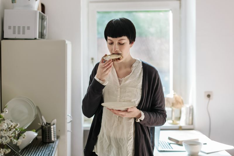 Young woman standing in her kitchen and eating a buttered bread.