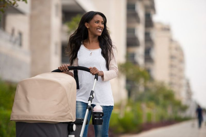 new mother walking with baby in stroller