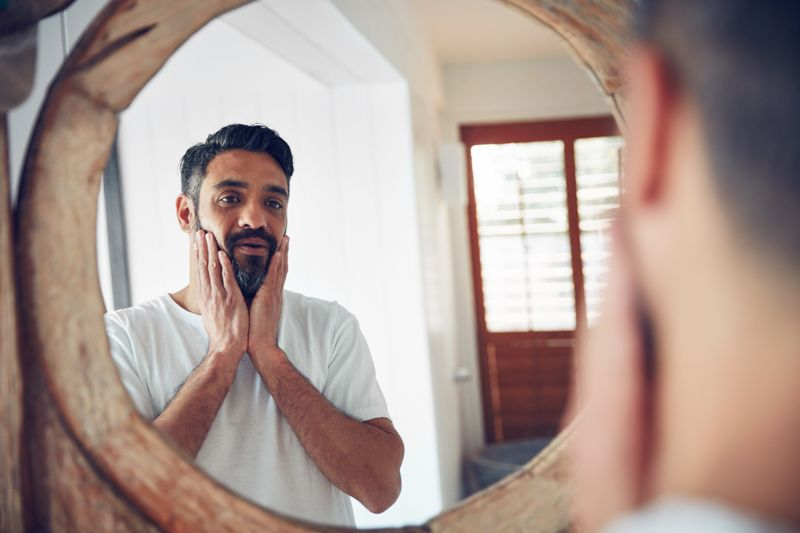 Shot of a mature man looking at his reflection the bathroom mirror