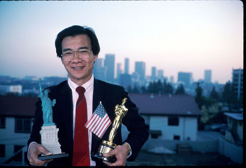 """051353 09: (NO NEWSWEEK - NO USNEWS) Dr. Haing S. Ngor holds a small Statue of Liberty and an Oscar outside his apartment April, 1988 in Los Angeles, CA. Ngor won the 1985 Best Supporting Actor Oscar for his portrayal of Cambodian photographer Dith Pran in the film """"The Killing Fields."""""""