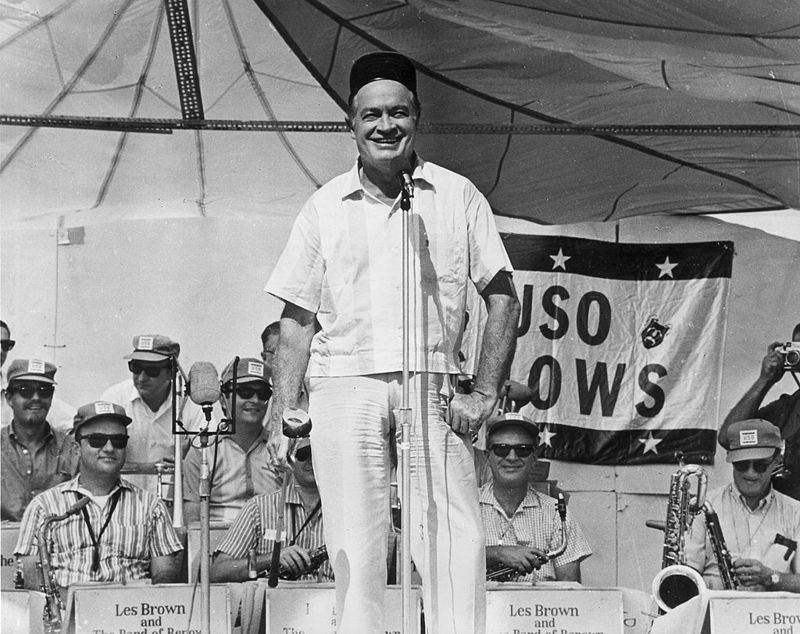 American entertainer Bob Hope holds a golf club as he stands on stage and smiles with Les Brown's band, during a 1967 USO show to entertain American troops overseas during the conflict in Vietnam.