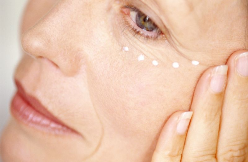 Mature woman applying cream to face, close-up