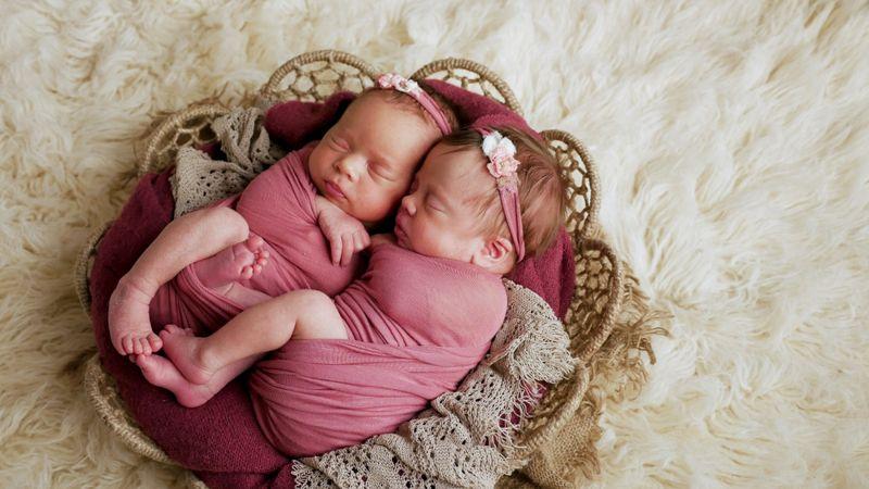 twin newborns swaddled in a basket