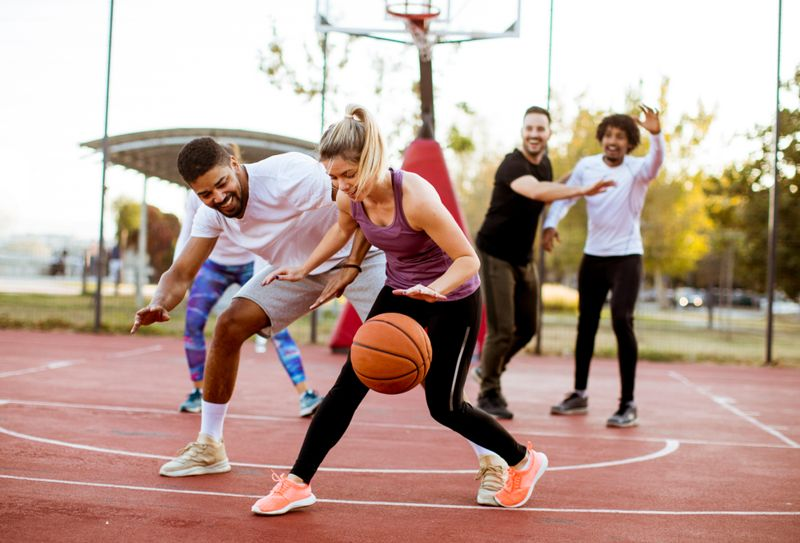 young woman playing basketball with male friends