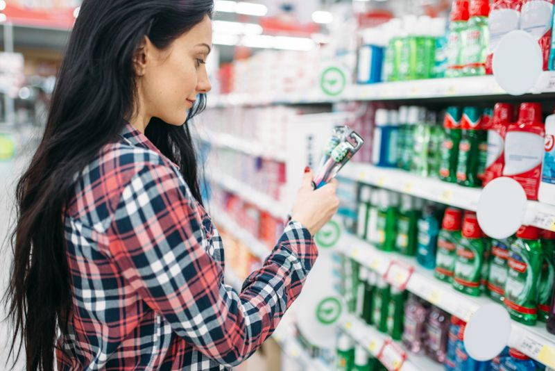woman choosing between toothbrushes at the store