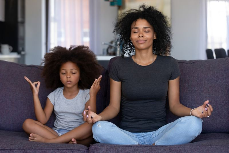 child and mom meditating in lotus pose