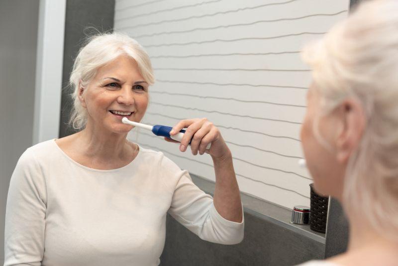 older woman brushing her teeth