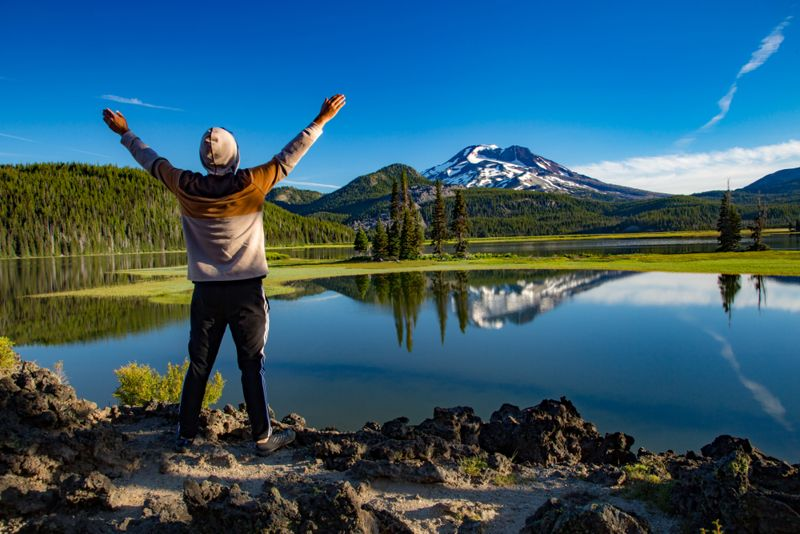 A young man offering praise to the south sister mountain, looking accross Sparks lake in the Oregon cascade mountains on century drive near Bend, Oregon