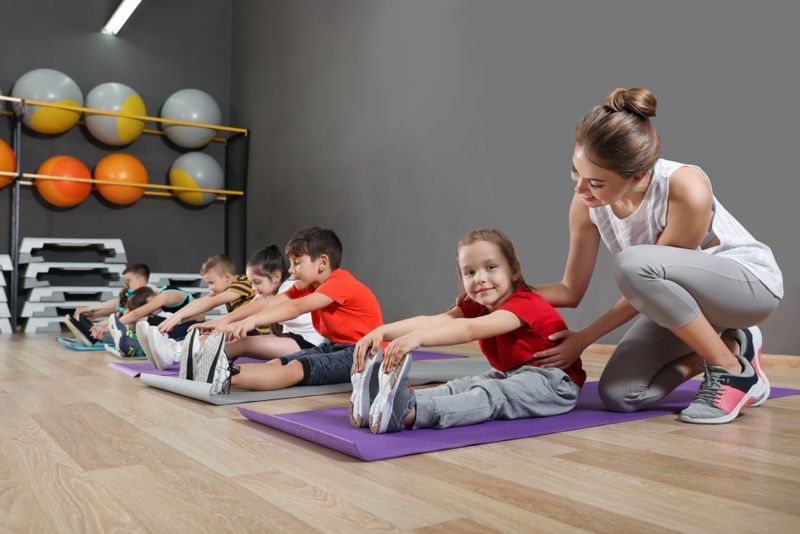 yoga teacher helping little girl in forward fold