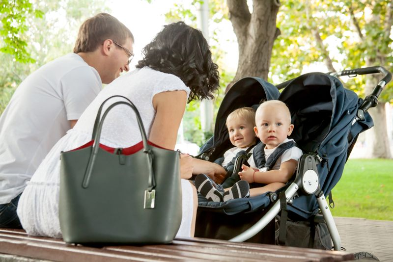 couple outside with baby twins in stroller