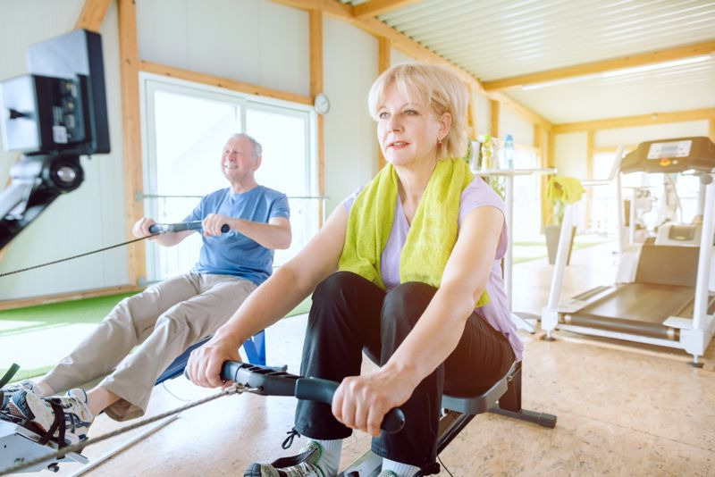 older woman and man using rowing machines at the gym