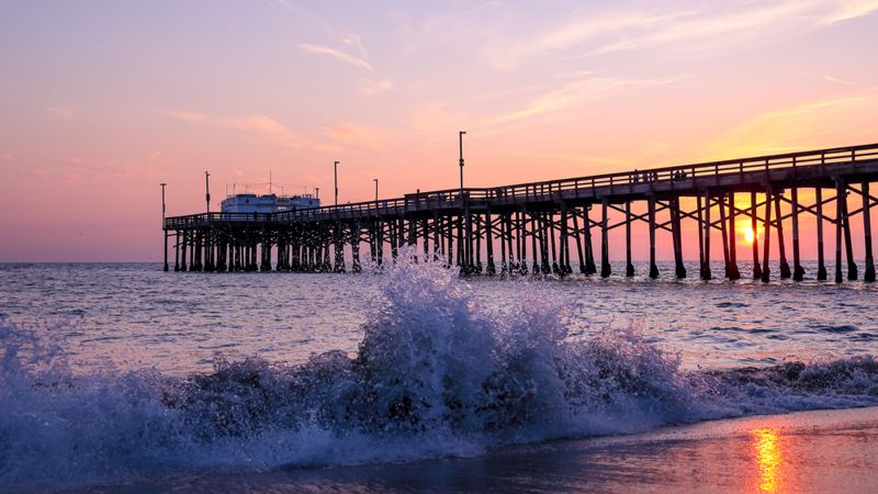 Scenic sunset over the Pacific ocean. A setting sun behind the long pier, Irvine, Orange County, California