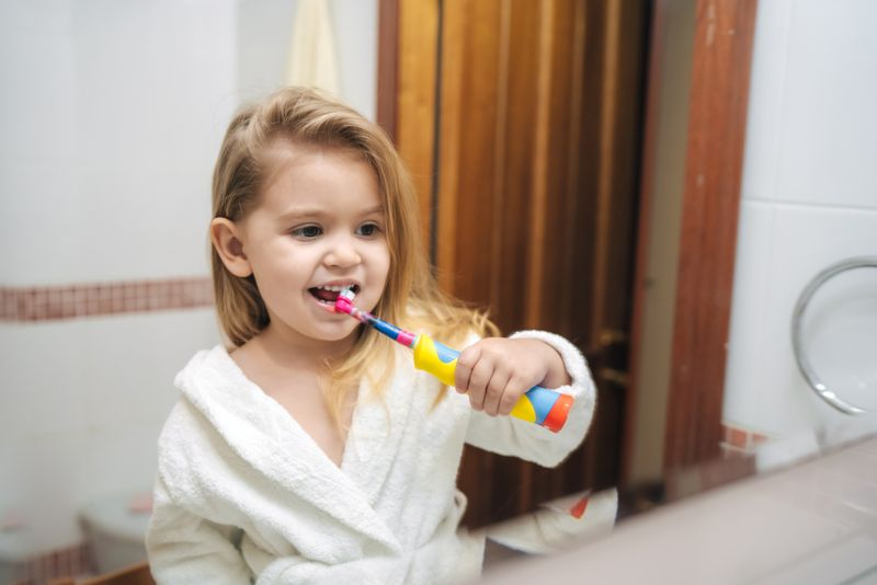 little girl brushing with an electric toothbrush