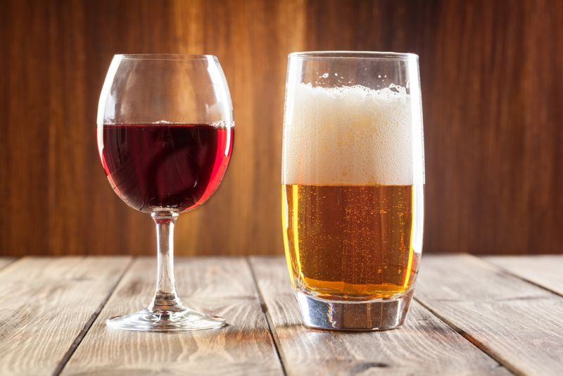 glass of red wine next to glass of beer
