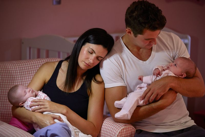 exhausted parents with newborn twins
