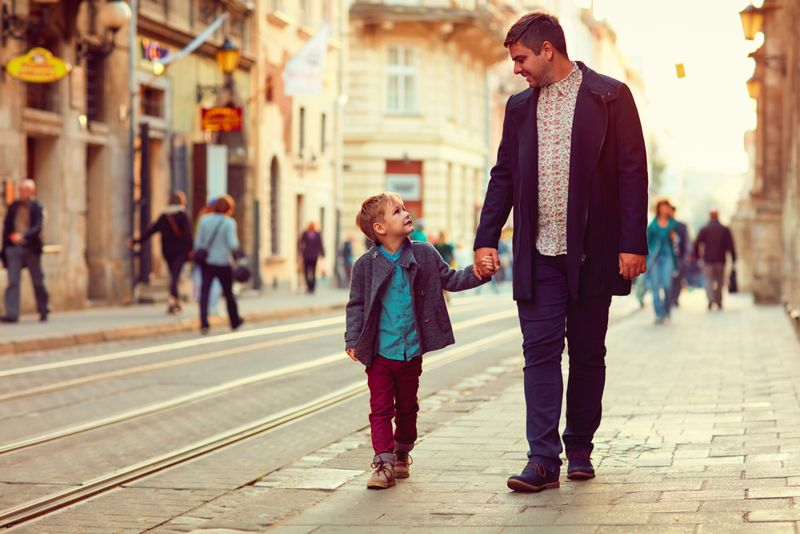father and son walking down street together
