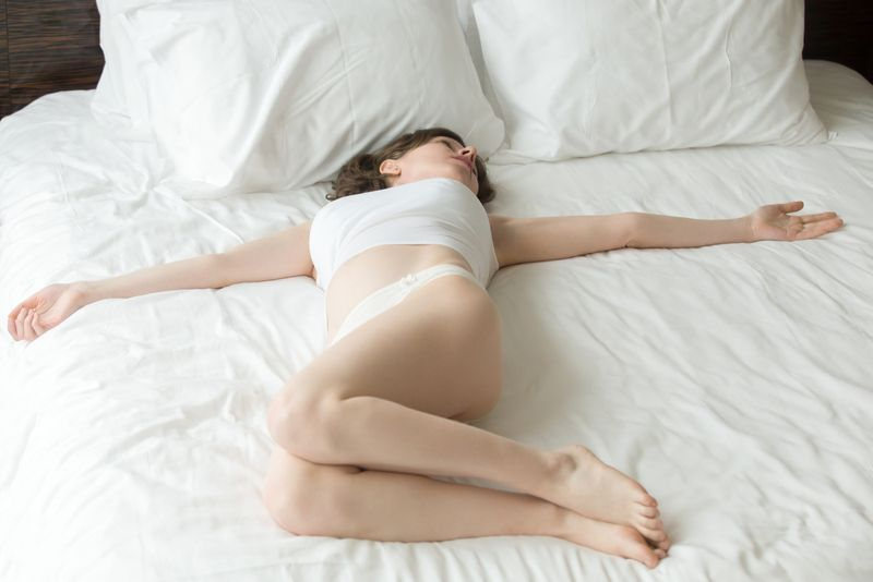 woman doing supine twists on her bed