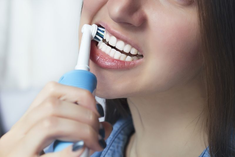 woman awkwardly brushing teeth with electric toothbrush