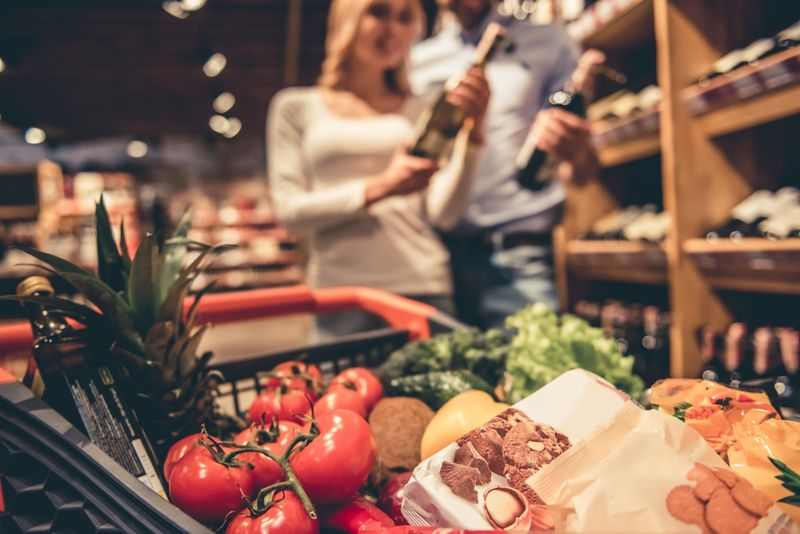 couple choosing wine at the grocery store with cart of vegetables