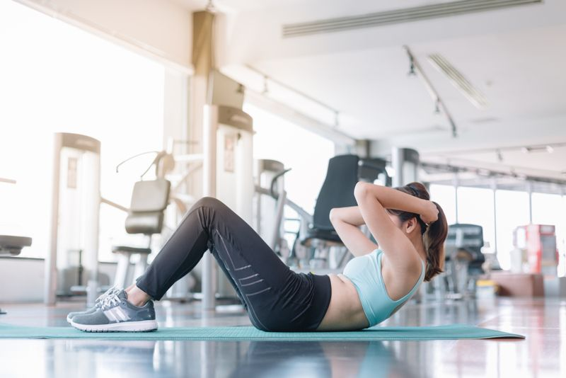 woman doing sit ups at the gym
